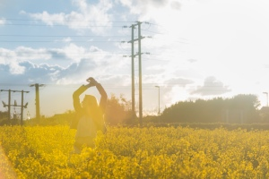 Girl Feeling Free In A Yellow Field At Sunset